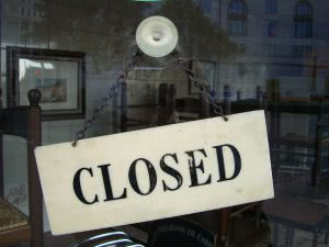"""Closed"" signage behind a glass wall."