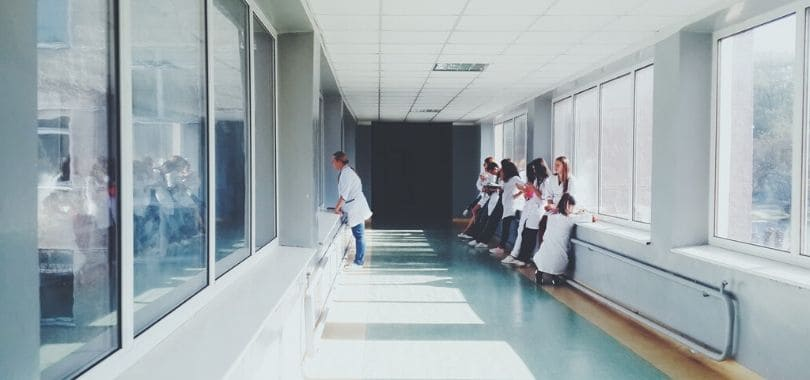 A white hospital hallway with people standing at the far end.