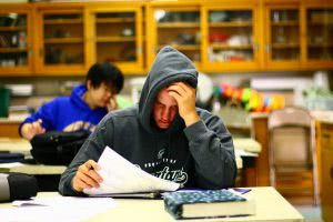 Frustrated student in a hoodie looking at his test results in a classroom.