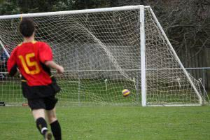 Back view of a soccer player hitting the goal.
