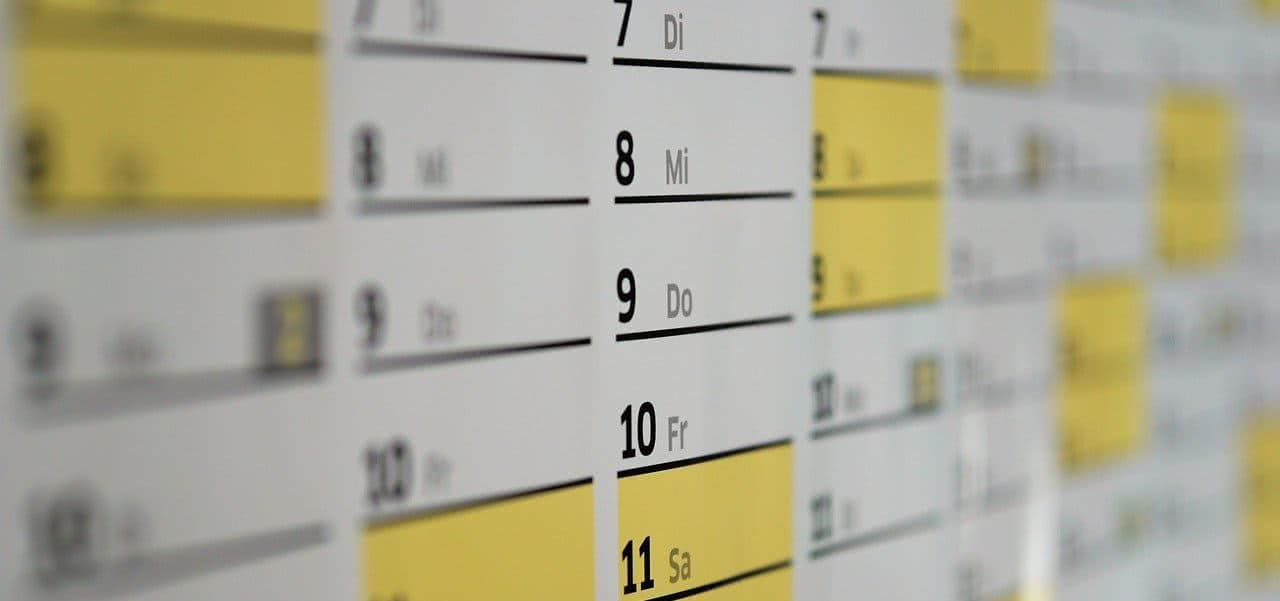 Close-up shot of a calendar with some days highlighted yellow.