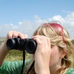 A blonde girl looking through binoculars in the field.