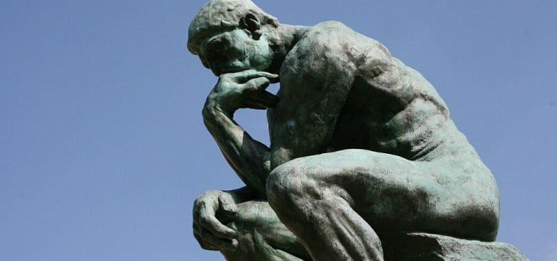 A statue of the Thinker against a blue sky.