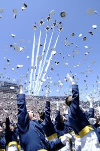 United States Air Force Academy students cheering while jet aircrafts flying above them.