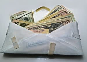 Wood carved and painted envelope with overflowing money.