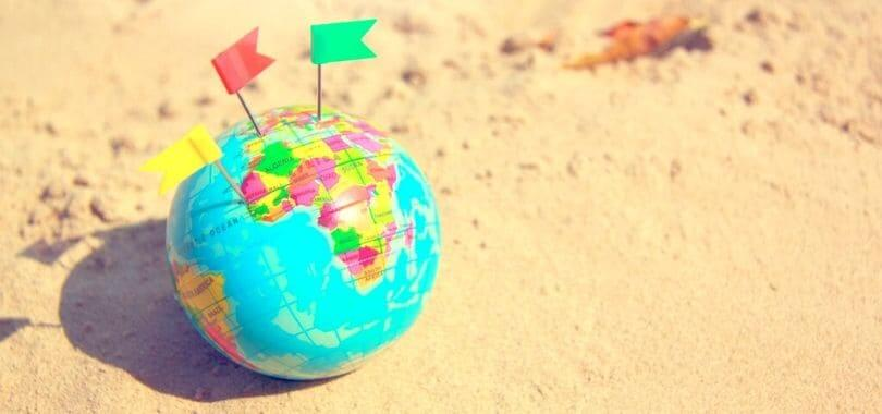 A small globe with colorful flags stuck in it.