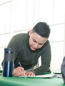A male student is writing on a paper on the desk.