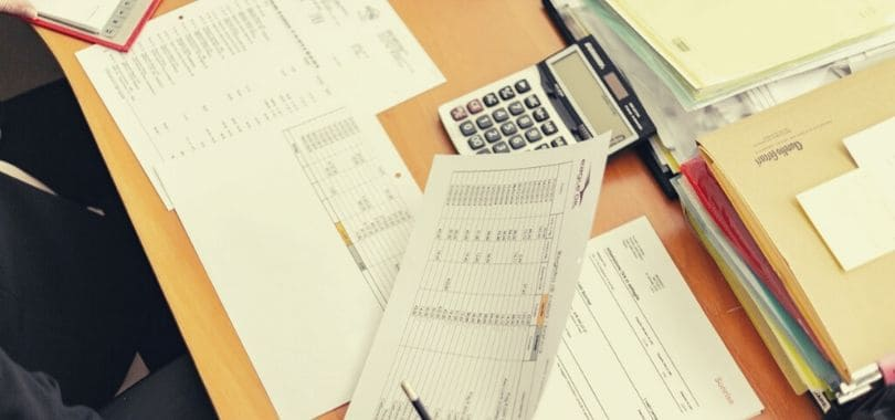 A desk covered in papers with a calculator.