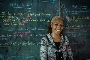 A female teacher is smiling in front of the green board with colorful chalks.