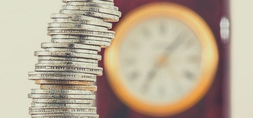 A stack of coins with a clock in the background.