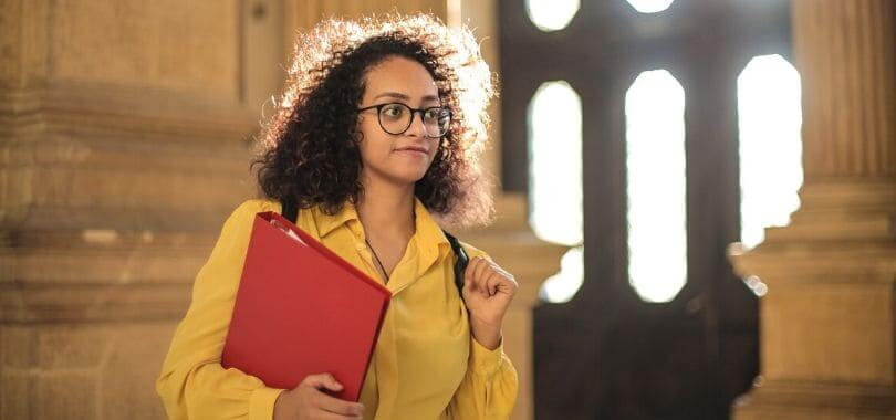 A student holding a red binder.