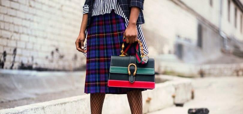 A model wearing a plaid skirt and holding a striped bag.