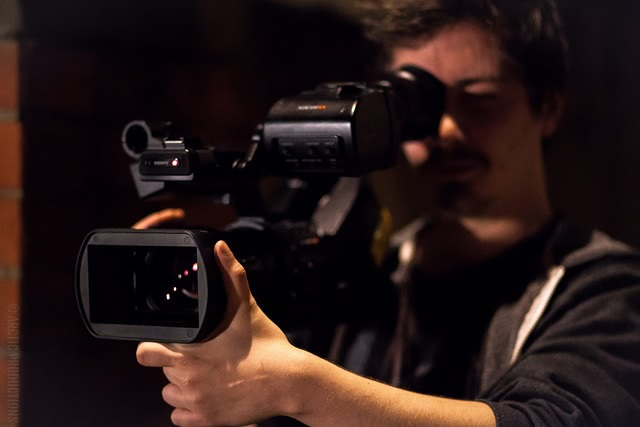 A film student looking through a black camera as he directs a scene.