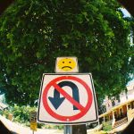 No U Turn signage with sad face above it.