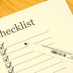 """A piece of paper that says """"checklist"""" with lines underneath and a pen sitting on top."""