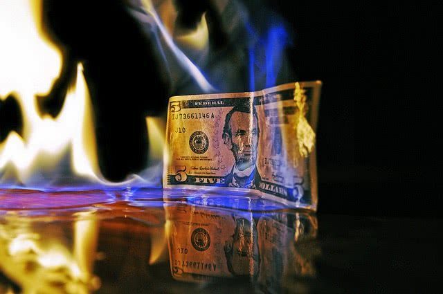 Five dollar bill burning with fire.