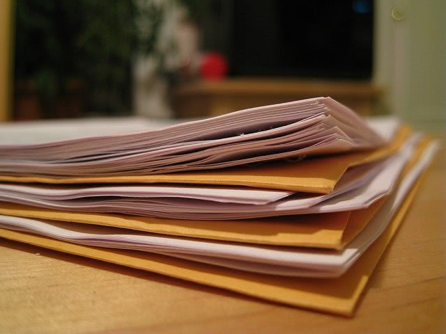 A pile of papers and manila folders on a desk.