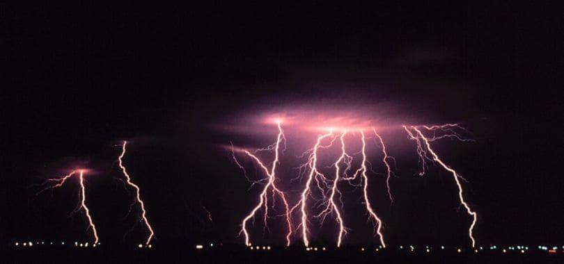 Lightning flashing at night over a city.