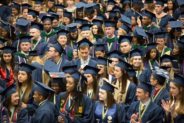 Crowd of student graduate class in caps and gowns.