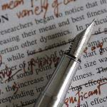 Like this pen and notes, proofreading your college essay can be messy but rewarding.