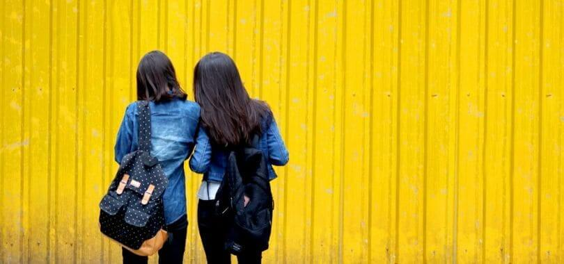 Two girls standing side by side against a yellow wall.