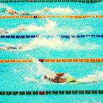 Four student swimmers competing in multiple pool lanes.