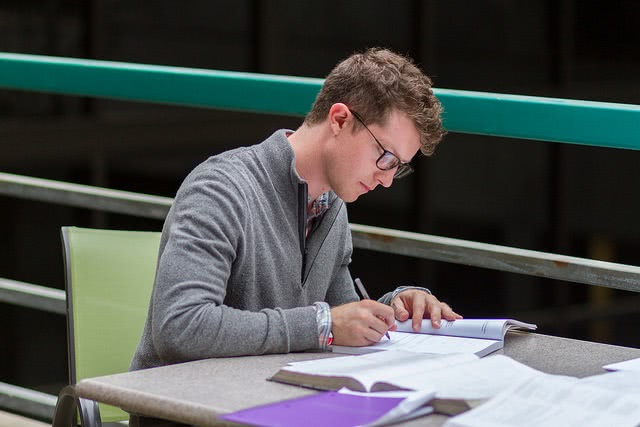 Male student studying at desk.