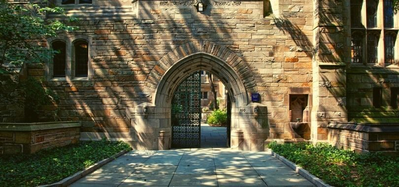 A metal gate with one door open on a college campus.