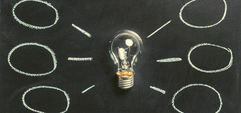 A light bulb on a chalkboard, with chalk circles around it.