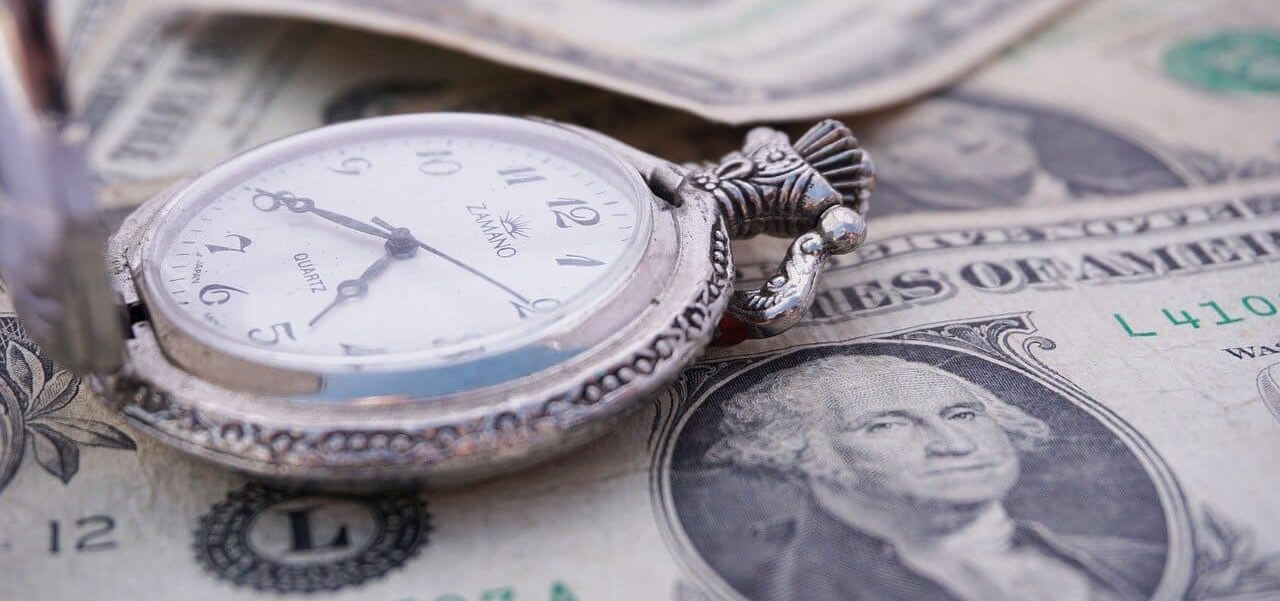 A stopwatch sitting on top of money.