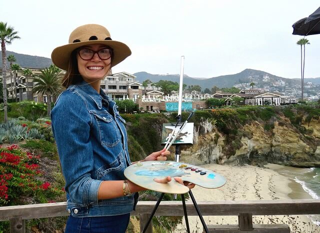 Girl holding a paintbrush and plate while standing at Montage Resort in the background.