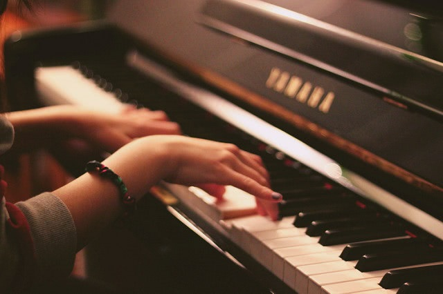 Close up of a girl's hands playing piano.