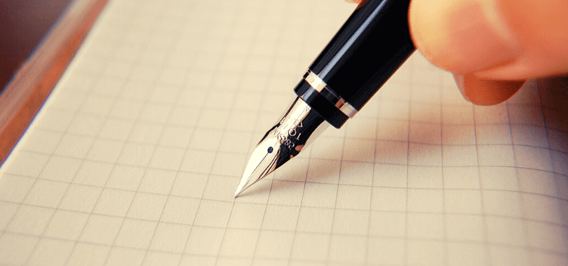A person holding a fountain pen against a piece of paper.