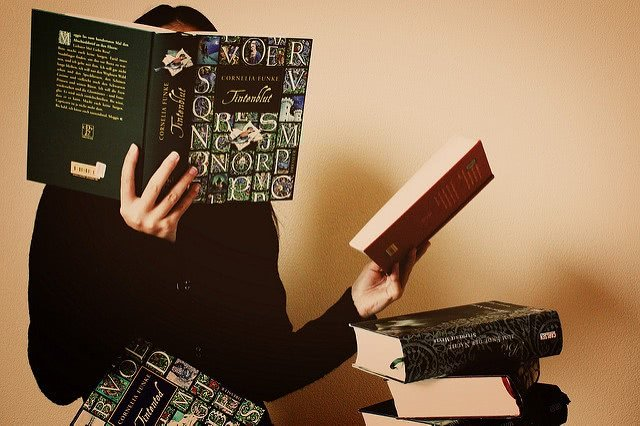 A girl covering her face with an open book while holding another book on the left hand.