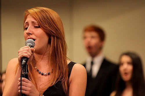 A girl singing and two backup singers blurred in the background.