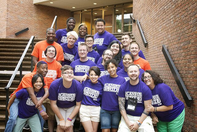 "Smiling alumni wearing violet and orange shirts that say ""Campus Pride""."