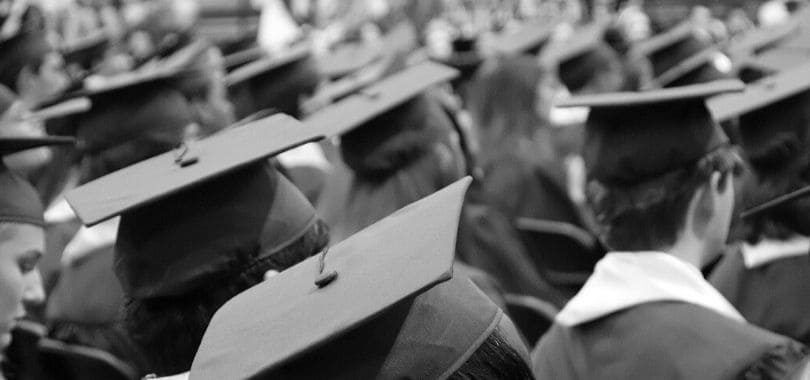 Students wearing graduation robes and caps standing together.