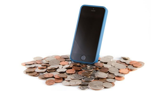 A smartphone is standing on a pile of coins.