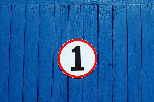 Circle number 1 placed on a blue wooden wall.