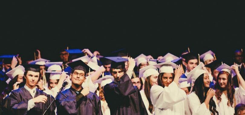 Students graduating, wearing robes and moving their tassels.