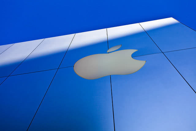 An Apple Store Building outdoors with a logo on the wall.
