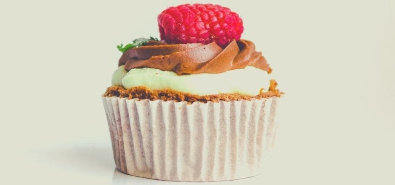 A chocolate cupcake with a raspberry on top.