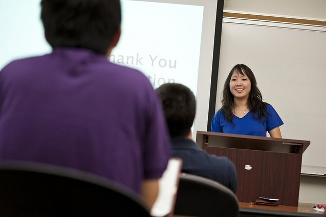Professor smiling and facing her students in the foreground.