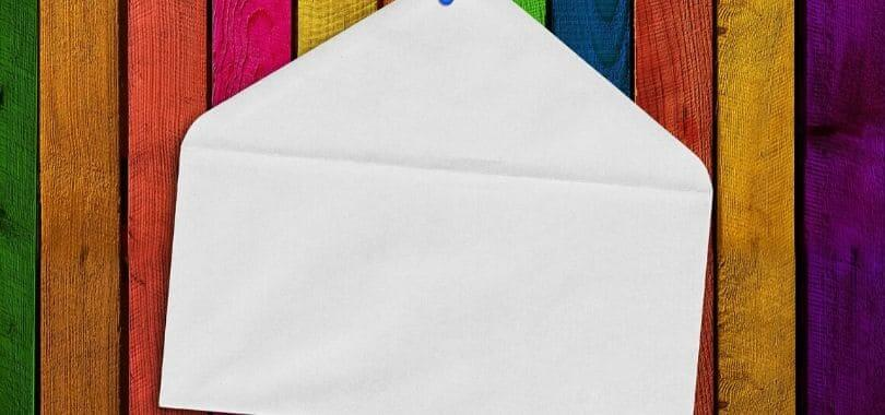 A white envelope pinned against a rainbow wooden board.