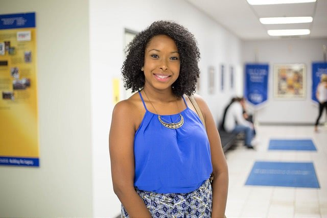 Image of a smiling black woman standing in the hallway.