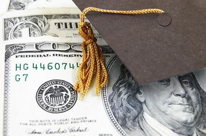 Graduation cap tassel covering the upper right side of one hundred dollar bill.