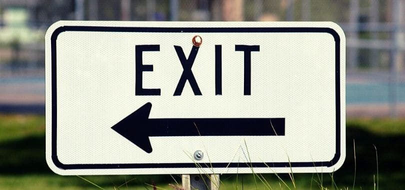 """A white sign with text that says """"exit"""" with an arrow pointing left."""