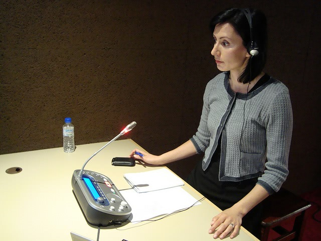 A woman wearing headphones while sitting at the desk with papers and audio gadget.