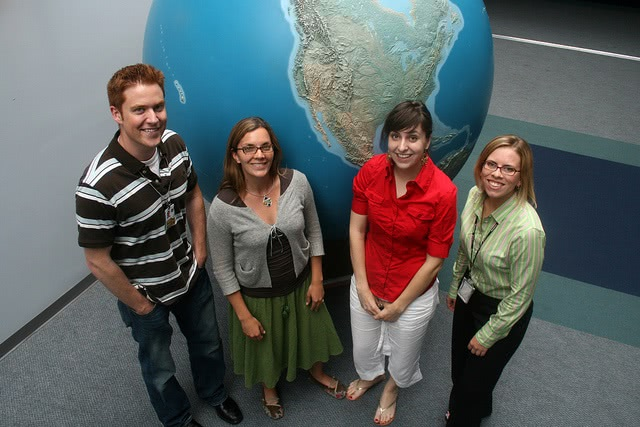 Students standing in front of a large globe.