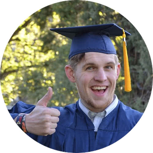Closeup of a smiling graduate student giving thumbs up.